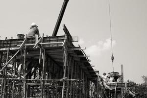 Monochrome picture of workers pouring mixed cement from a steel bucket hanging from a crane photo