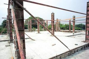 Perspective of concrete columns in the steel model standing on the cement floor at the construction site with clear sky background photo