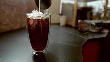 barista versant du lait dans un verre de café glacé video