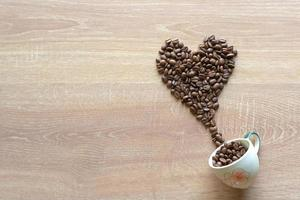 Many roasted coffee beans into a heart shape with a ceramic cup photo
