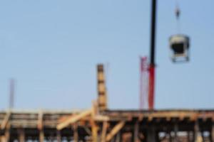 Defocused picture of crane carrying the mixed cement metal bucket at the construction site with blue sky background. Picture is blurred on purpose photo