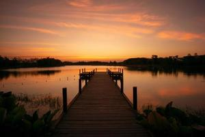 Wooden walkway into the lake with natural scenery of sunset and silhouette of forest in background photo