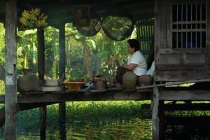 Ratchaburi, Tailandia - 25 de noviembre de 2018 - estilo de vida del pueblo tailandés en una zona urbana. una mujer está cocinando comida a flote en su casa. el memorial del rey rama ix foto