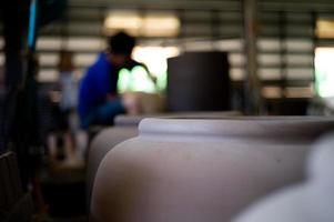 Closeup picture of traditional clay pottery in the factory with blurred worker working in background photo