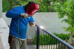 Closeup retrato de soldador con máscara soldando la estructura de acero de la valla negra con chispas de luz y humo foto