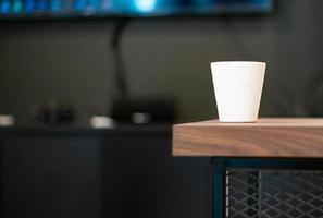 Closeup white cup without screen on the surface for adding some text puts on the wooden table with blurred electronic equipments in background photo