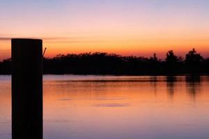 Silhouette of nail in the wooden pole at the pier with lake and sunset sky in background photo