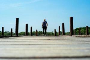 Back portrait of handsome man in casual cloth stands on wooden bridge with blue sky background photo