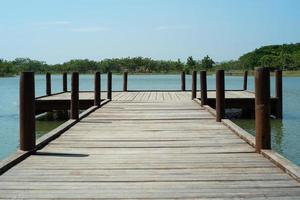 Wooden bridge into the lake with trees and horizontal line in background photo