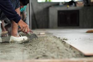 Hand installing the floor tiles by trowel at the construction site photo