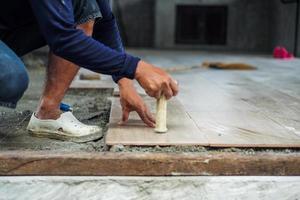 El enfoque selectivo en la mano del trabajador que instala la baldosa con el movimiento de la mano borrosa en el sitio de construcción foto