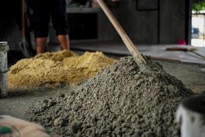 El enfoque selectivo en la superficie de la pila de cemento mixto con fondo borroso de arena en el sitio de construcción foto