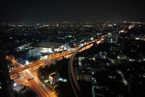 Cityscape of the city at night with the light trails from trains and traffic on the road photo