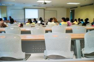 Selective focus on row of empty chairs with blurred group of students in background photo