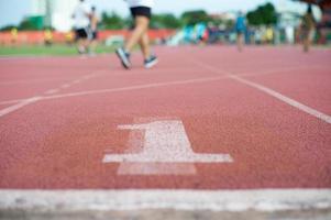 Textura abstracta y fondo de pista de atletismo vacía con el número uno en el suelo y gente desenfocada haciendo ejercicio en segundo plano. foto