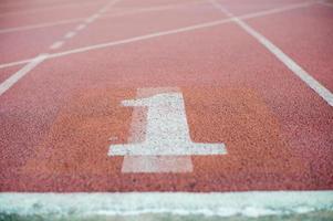 Textura abstracta y fondo de pista de atletismo vacía con el número uno en el suelo foto