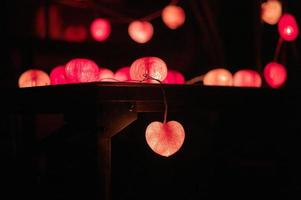 Closeup of heart-shaped LED lights decorated in the darkroom photo