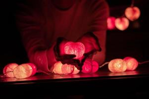 Man holds heart-shaped LED light lamp in his hands in a dark room photo