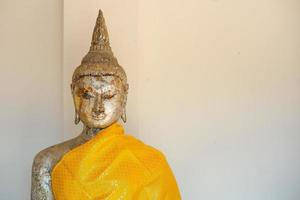 Closeup eye and face of golden Buddha statue coated by the golden leaf at the Buddhism temple photo