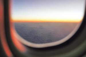 La luz del atardecer en el horizonte con fondo de cielo azul y la sombra de la ventana de un avión en primer plano foto
