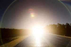Sun on a road with lens flare photo