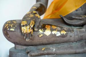 Selective focus on closeup hand of Buddha statue coated by the golden leaf photo