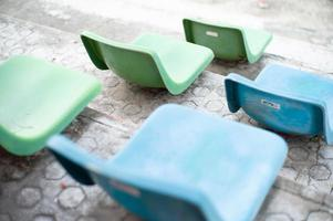 Selective focus on rows of plastic chairs installed on the cement steps of an outdoor stadium photo