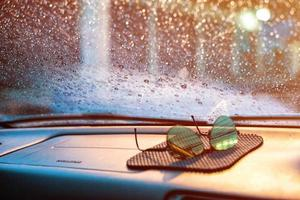 Raindrops and moisture on the car's front glass with blurred sunglasses in foreground. photo