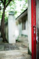Selective focus on red steel frame of door with blurred glittering bokeh light and tree in background photo