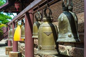 Selective focus on brass bells hanging on the steel bar at Buddhism temple photo