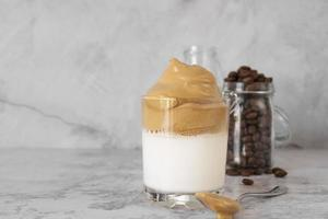 Glass of dalgona coffee on table photo