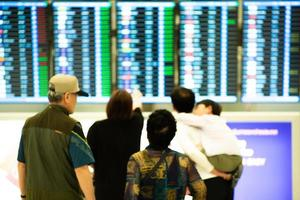 Blurred group of people standing in front of and looking at the flight schedule monitor photo