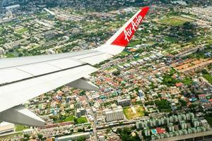 Bangkok, Tailandia - 8 de junio de 2020 - Primer ala de un avión de Air Asia mientras volaba en el aire con el paisaje urbano debajo foto
