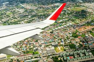 Closeup wing of airplane while flying in the air with cityscape below photo