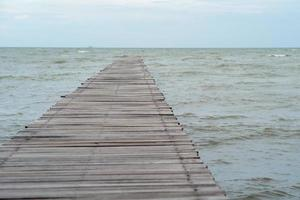 Abstract texture and background of wooden walkway into the sea. Wood bridge at the shore into the ocean photo