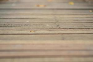 Abstract texture and background of wooden walkway with blurred leaves on the floor photo