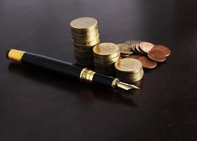 Close up for Fountain pen and coins stack for loan money concept photo