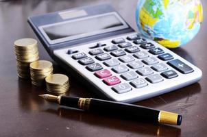 Fountain pen and calculator money coins stack and earth for Business concept photo