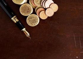 Fountain pen and Money coins stack on wooden table for finance concept background bove photo