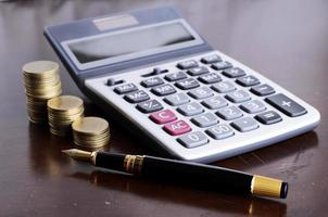 Fountain pen and calculator and coins stack on wooden table for loan money concept photo