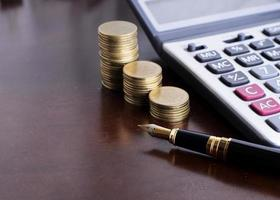 Fountain pen and Money coins stack and calculator for finance concept photo