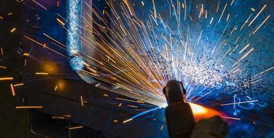 Welder, or craftsman, erecting technical industrial steel in factory photo