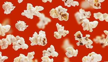 Delicious popcorn grains closeup on red background photo