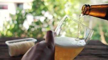 verser la bière de la bouteille dans un verre à l'arrière-cour video