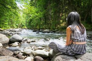 Woman sitting on a rock looking at a river photo