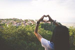 Making making a heart shape with hands with a city in sight photo