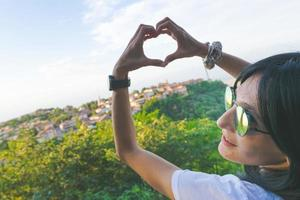 Woman putting hands into a heart shape in front of a city photo