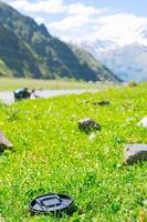 Lens cap in grass with mountains photo