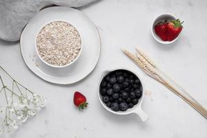 Oatmeal with fruit on white table photo