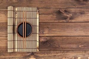 Mat for sushi and chopsticks on wooden background photo